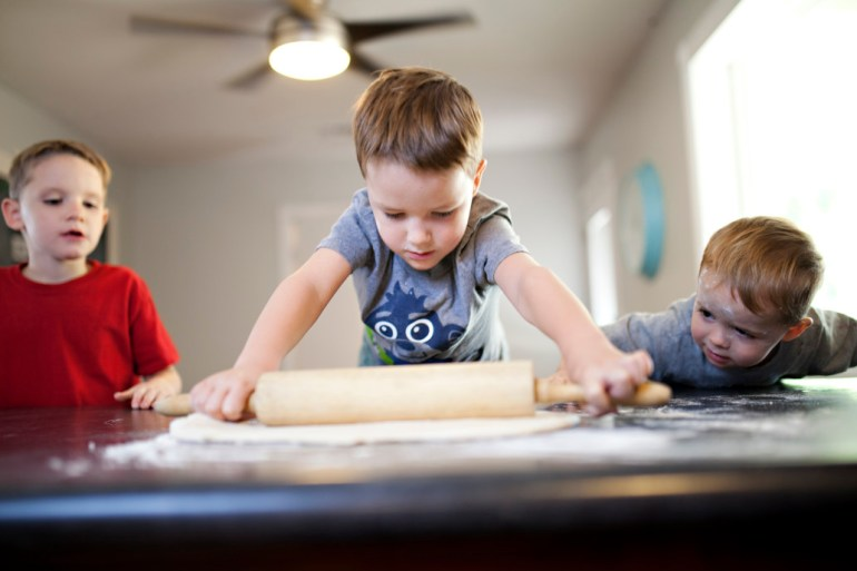 3 childrens making pizza bases rolling dough