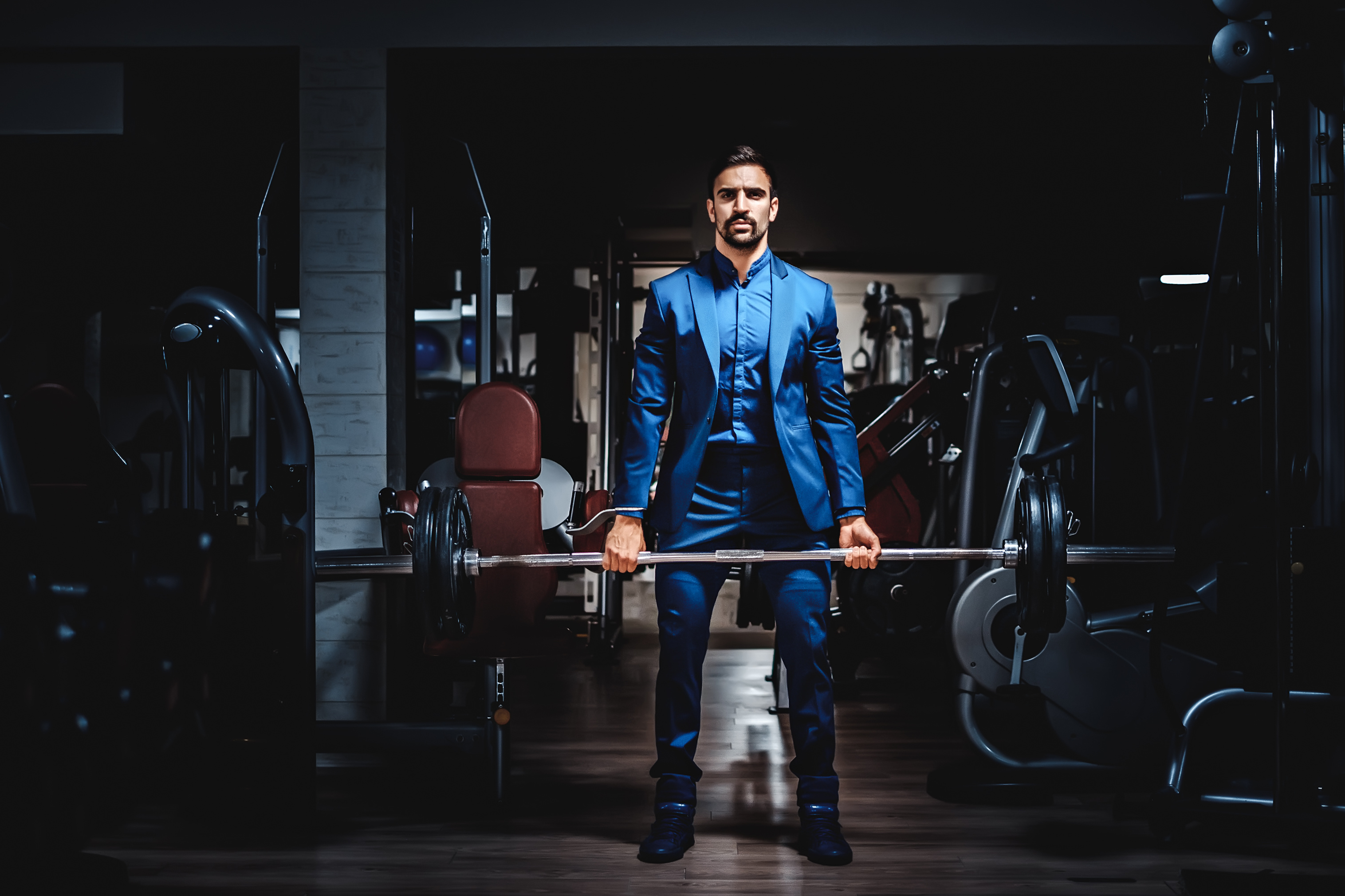 Man in suit lifting heavy weight