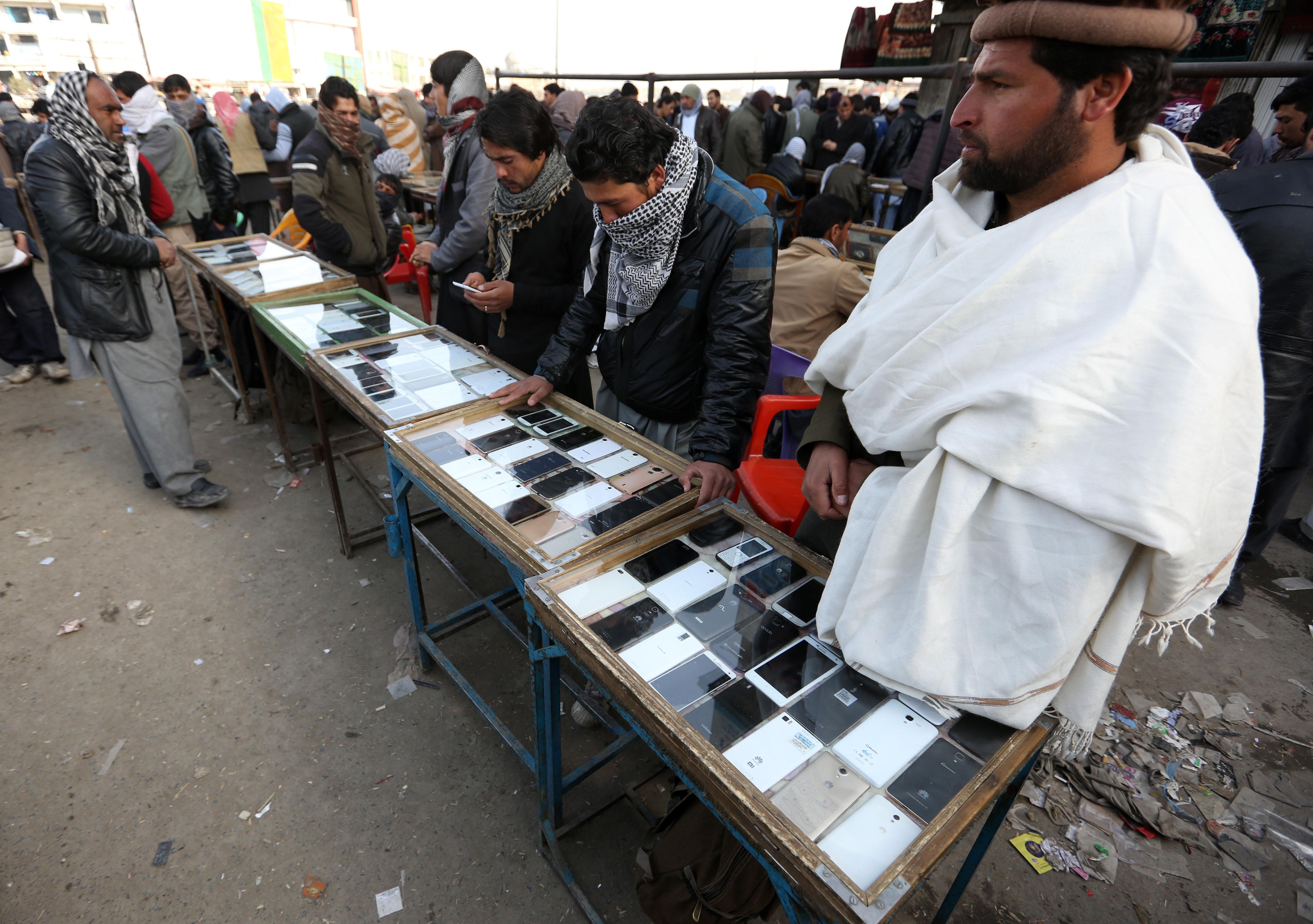 Afghan vendors selling smartphones wait for customers at a market in Kabul, Afghanistan. Image: AP Photo/Rahmat Gul