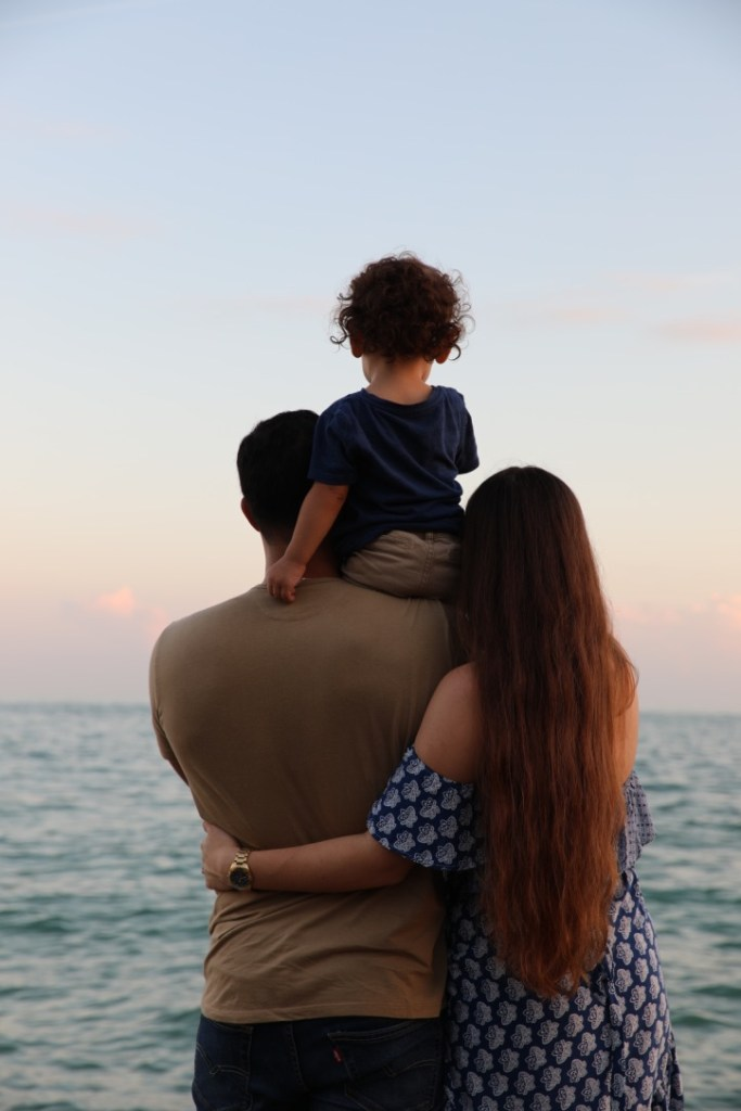 family of three looking out to the ocean at sunset