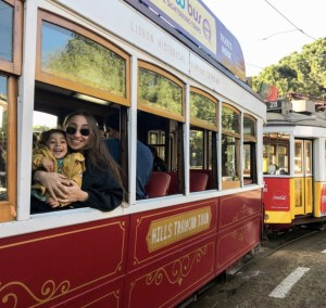 Mother and son riding red tram in Lisbon