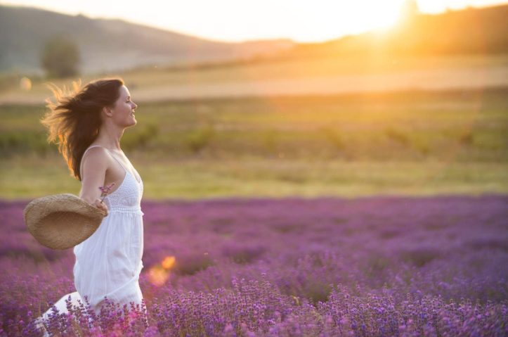 Beautiful young healthy woman with a white dress running joyfully through a lavender field holding a straw hat under the rays of the setting sun.
