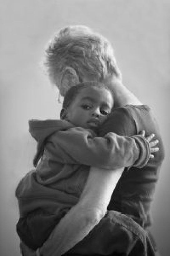 woman cuddling a young boy