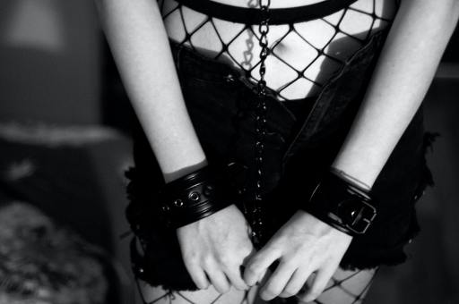 Victim of sex trafficking; Teen girl in  disheveled fishnet stockings, a short skirt, and chained in handcuffs