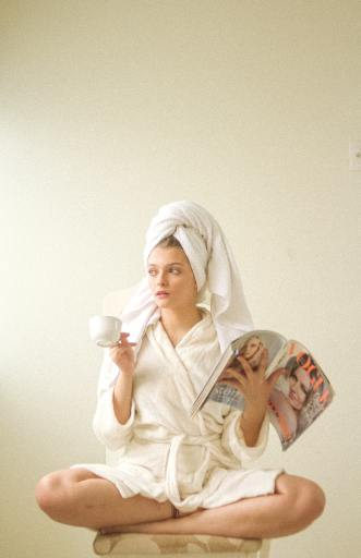A woman sits cross legged on an ottoman, wearing a bathrobe and a towel on her head. She sips tea and reads a Vogue magazine as part of her self care routine.