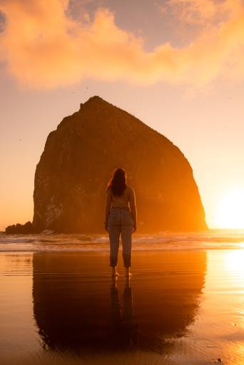 A woman stands with her back to the viewer facing a mountain in the sunset.