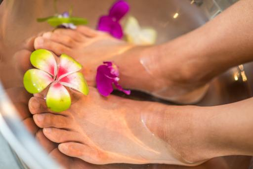 A woman soaks her feet in floral infused water as a part of her self care routine.