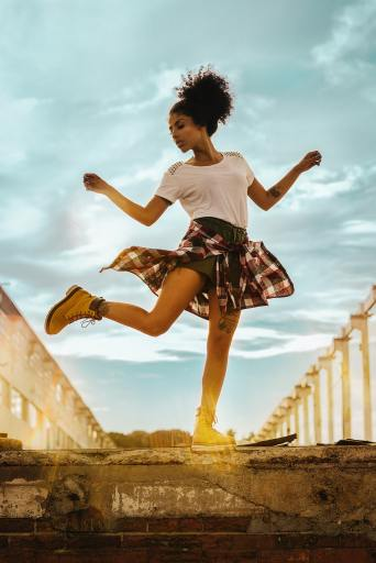 A teen girl practices dance moves on concrete steps.