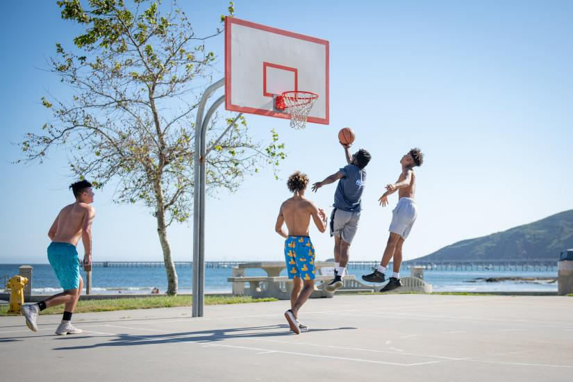 A group of teens plays basketball on an outdoor court at a community center