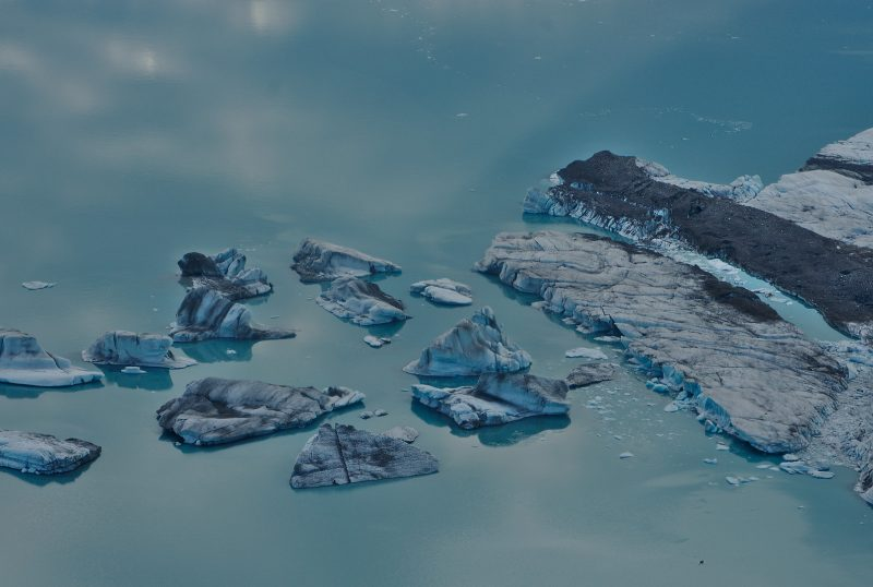 Large, irregular chunks of ice floating in light blue water.
