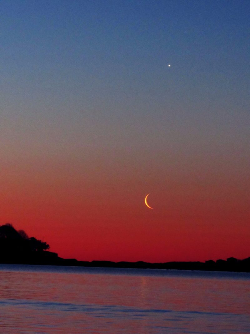 Red morning twilight over calm ocean, with slim crescent moon and bright dot (Venus) above.