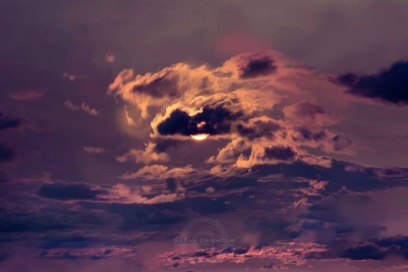 Torn-looking clouds around the moon.
