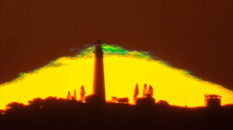 Yellow pyramid with tall tower silhouetted in center and bright green top.