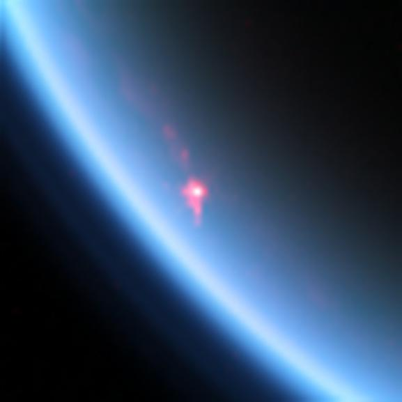 Section of Titan with pink patch on blue atmosphere, white dot in pink patch.