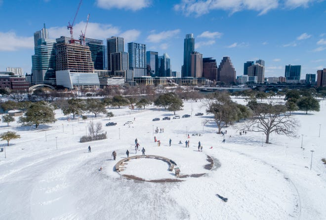 People play in the snow at Butler Park on Feb. 15. A historic winter storm swept Texas in February, crippling infrastructure and leaving millions without power. What role did global warming play?