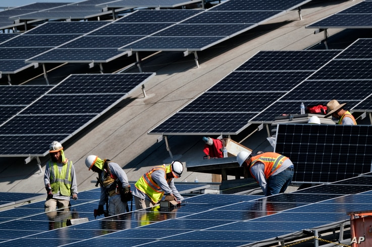 In this Thursday, Aug. 8, 2019 photo a workers install solar panels onto a roof at the Van Nuys Airport in the Van Nuys section…