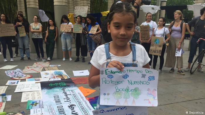 Girl holding sign that says There is still time to protect our forests