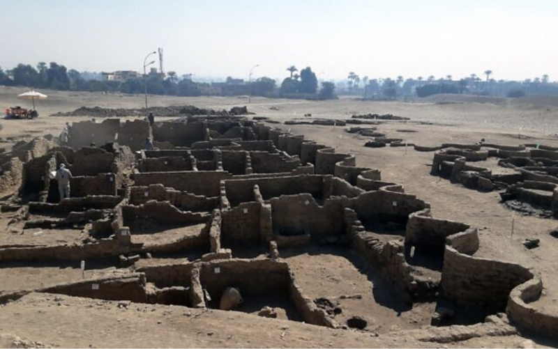 Ruins of a city with mud walls and structures.