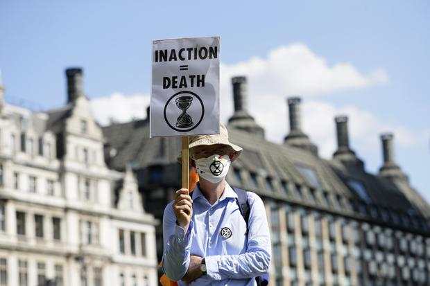 A demonstrator holds a poster during an Extinction Rebellion climate change protest (Kirsty Wigglesworth/AP)