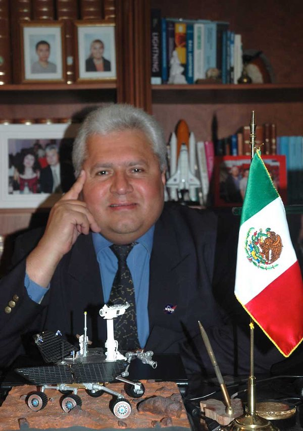 Silver-haired man in suit sitting at desk with rover model and Mexican flag.