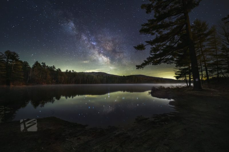 Starry cloud over lake with low-level fog, stars reflected in extremely calm lake.