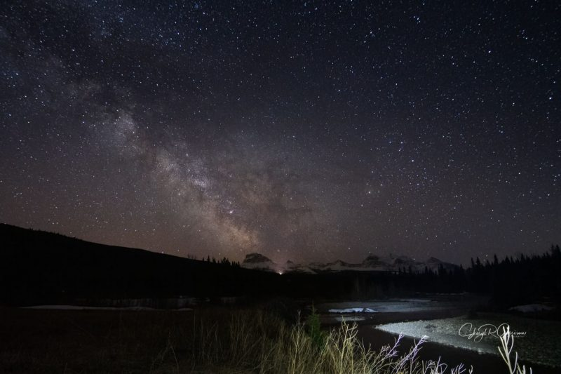 Milky Way cloud stretching across sky with rugged snow-capped mountains in the distance.