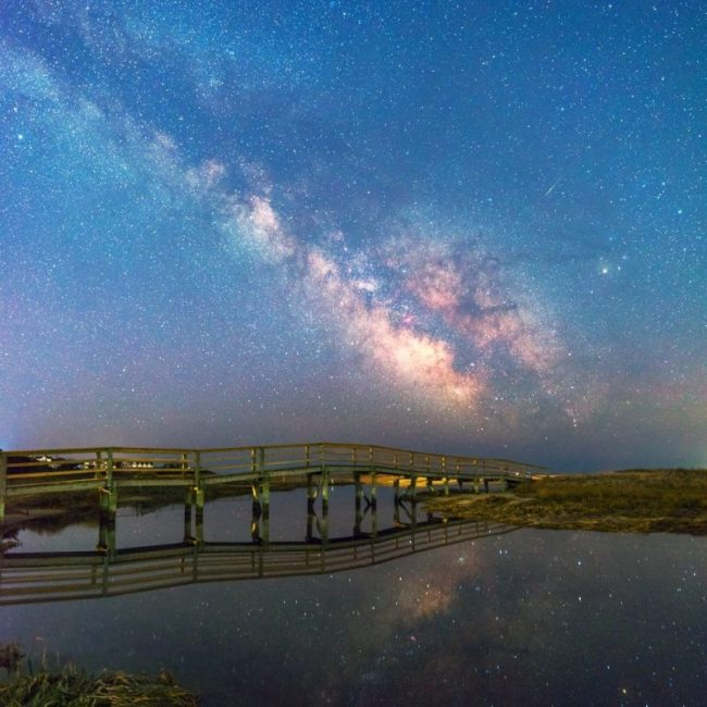 The Milky Way reflected clearly in body of water with bridge in foreground.