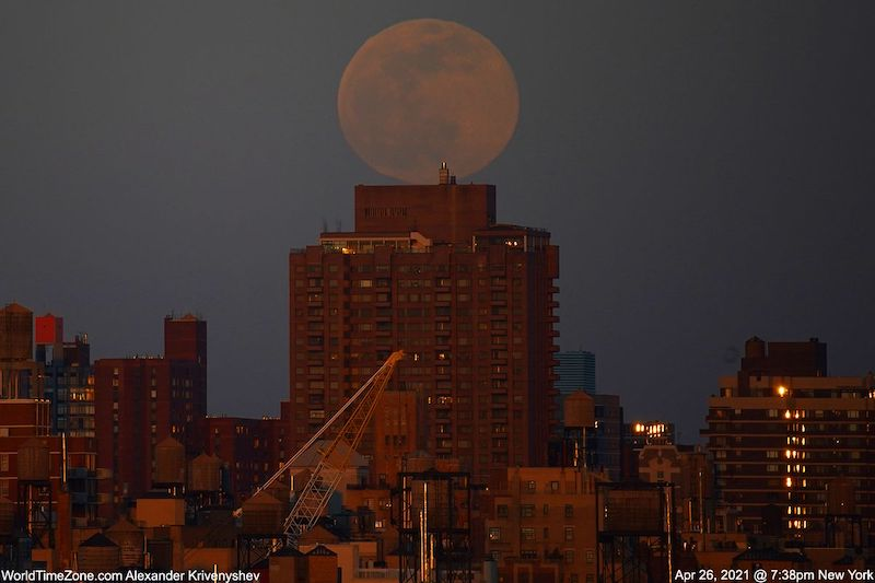 Large and faint full moon seemingly resting on top of a reddish high rise building.