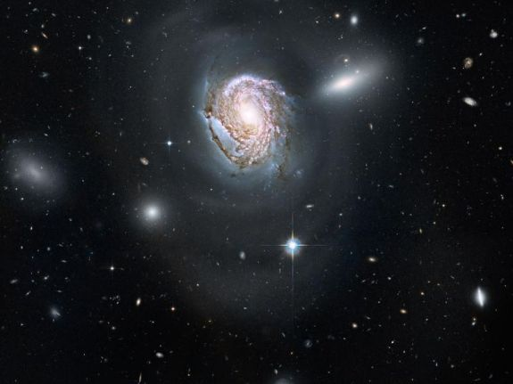 Detailed spiral galaxy with other galaxies in background.