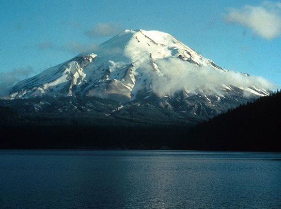 Snowcapped mountain with water in foreground.