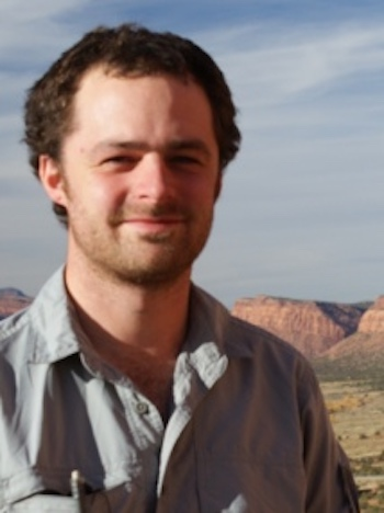Smiling young man with rocky hills behind him.