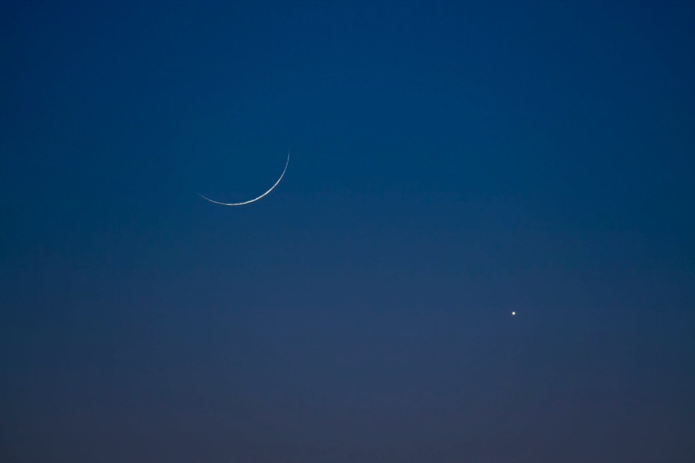 Very young thin crescent moon, with bright planet Venus, in deep blue sky.