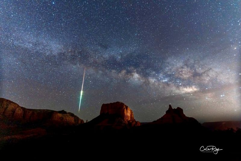 Red rock formations with star cloud and bright streak of light above.