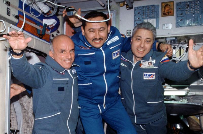 Three people are seen floating in their astronaut uniforms aboard the ISS with technical equipment in the background.