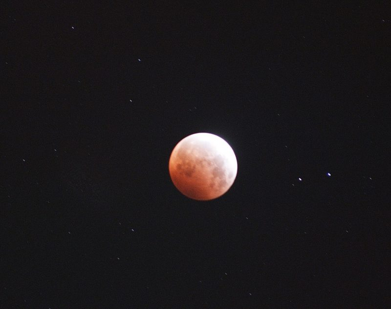 Lunar eclipse: Shining orange and white ball on a black background.