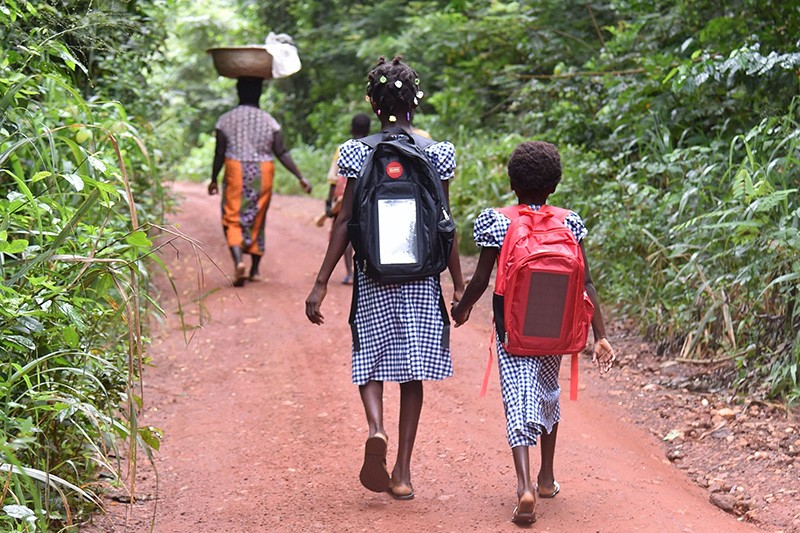 Ivorian schoolchildren walk to school carrying backpacks fitted with a connected lamp powered by solar panels