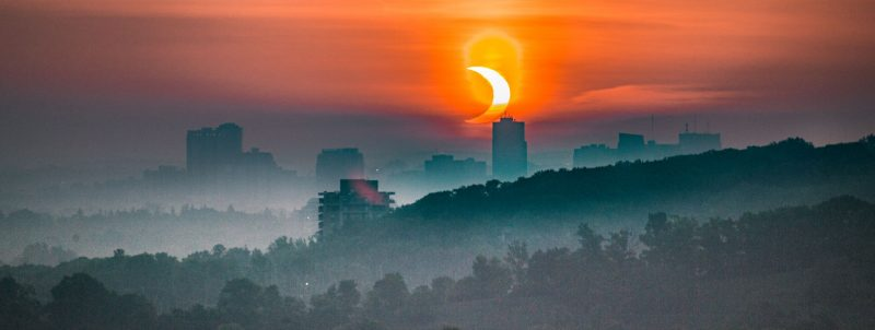 Cityscape in foreground of eclipsed sun.
