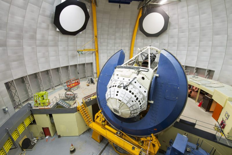 The view from inside a telescope dome, showing a large camera mounted on a telescope.