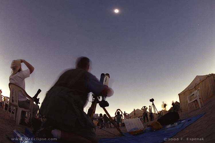 Silhouette of man at telescope, gazing toward an eclipsed sun, observing the sun safely.