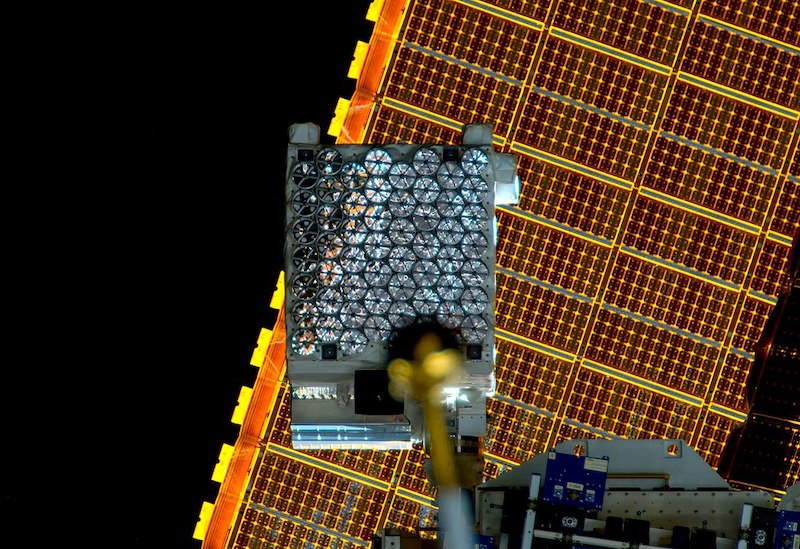 Telescope instrumentation mounted on the International Space Station, seen in front of solar panels.