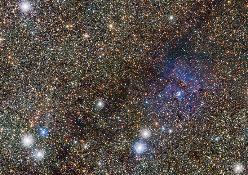 Dense star field including larger brighter stars and a diagonal dark band of dust stretching over the image.