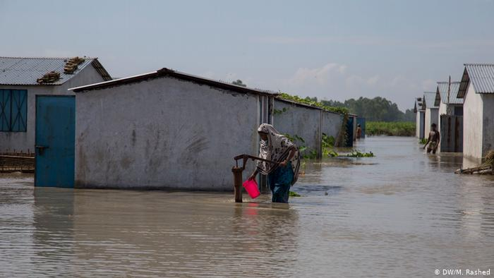 A local resident wades through knee-high water carrying a red colored bucket