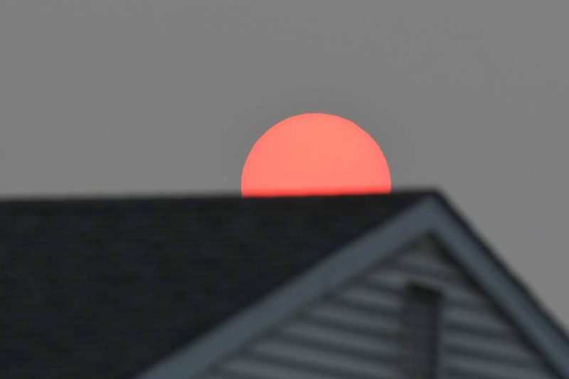 A very red sun over the roof of a house.