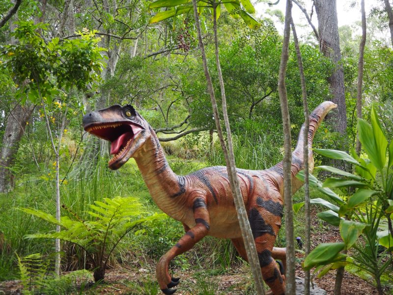 Recreate dinosaurs from their DNA: Striped predatory dinosaur with open mouth moving through trees.