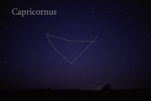 Roughly triangular arrangement of stars with lines between them, against faintly starry sky.