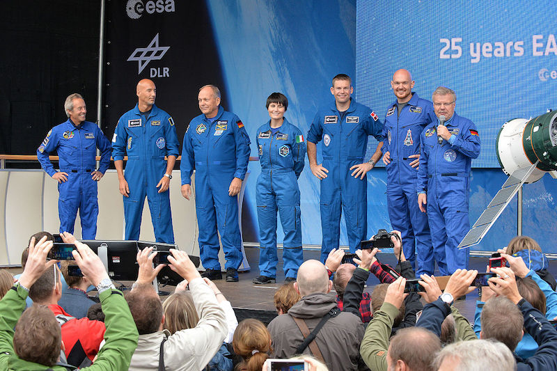 ESA; Seven people in blue suits stand in a line on a stage. One is speaking into a microphone.