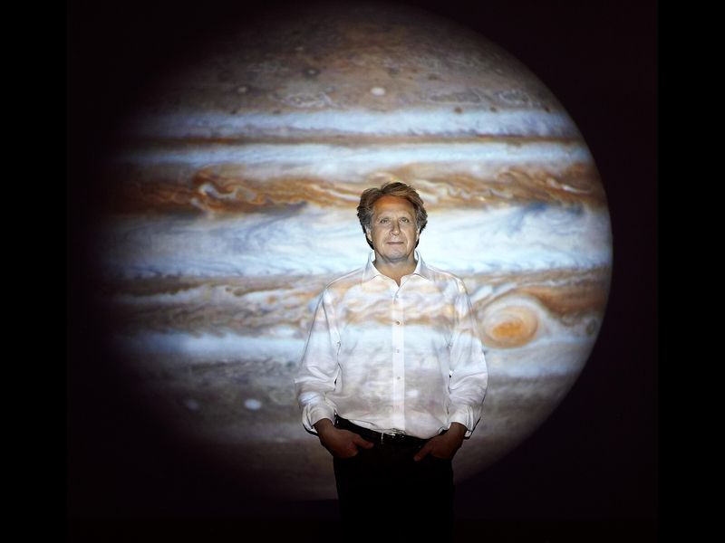 Man standing in front of projected image of Jupiter.