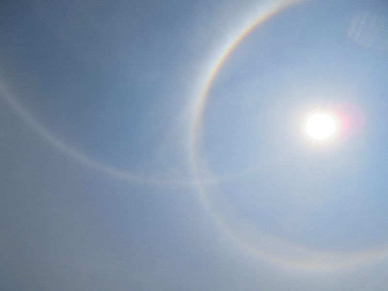 The sun to one side, with a 22-degree halo around it, and a 2nd arc, the parhelic circle, extending from the halo.