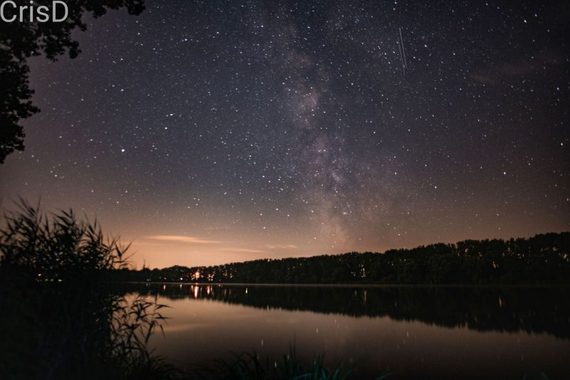 Milky Way over lake with two vertical meteors next to it.