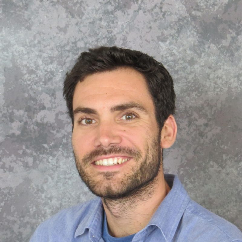 Smiling middle aged man with dark hair and short beard, wearing a blue open collar shirt.